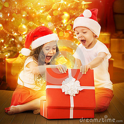 happy-kids-santa-hat-opening-gift-box-colorful-lights-christmas-tree-background-holidays-christmas-new-year-x-47547808